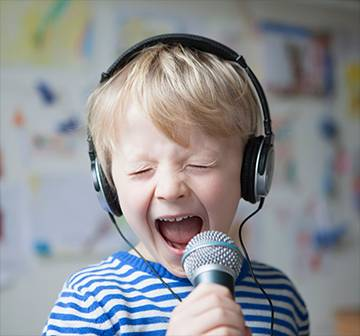 A child wearing headphones and singing into a microphone