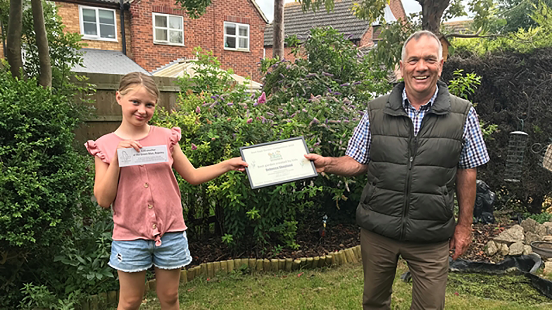 Garden expert John Stirland presents a certificate to Rebecca Shopland, winner of the Best Garden Created by Kids category in the Ropsley online garden competition